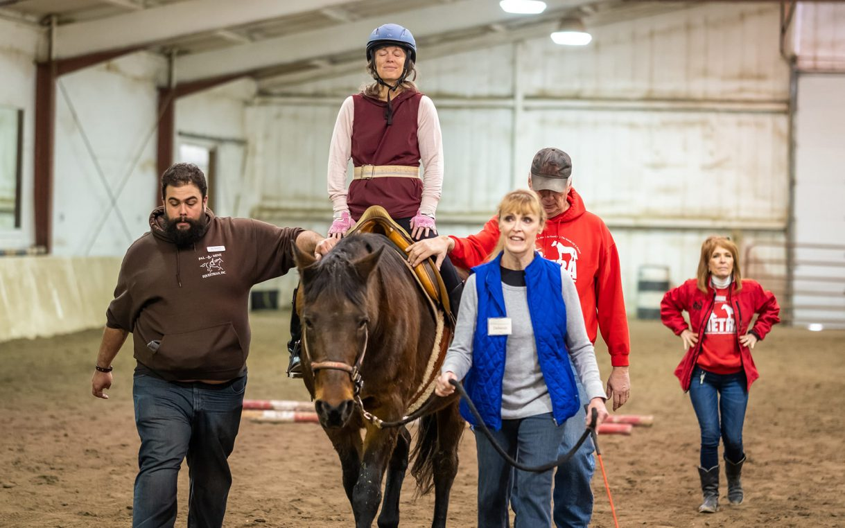A woman riding a horse with a team of therapists helping