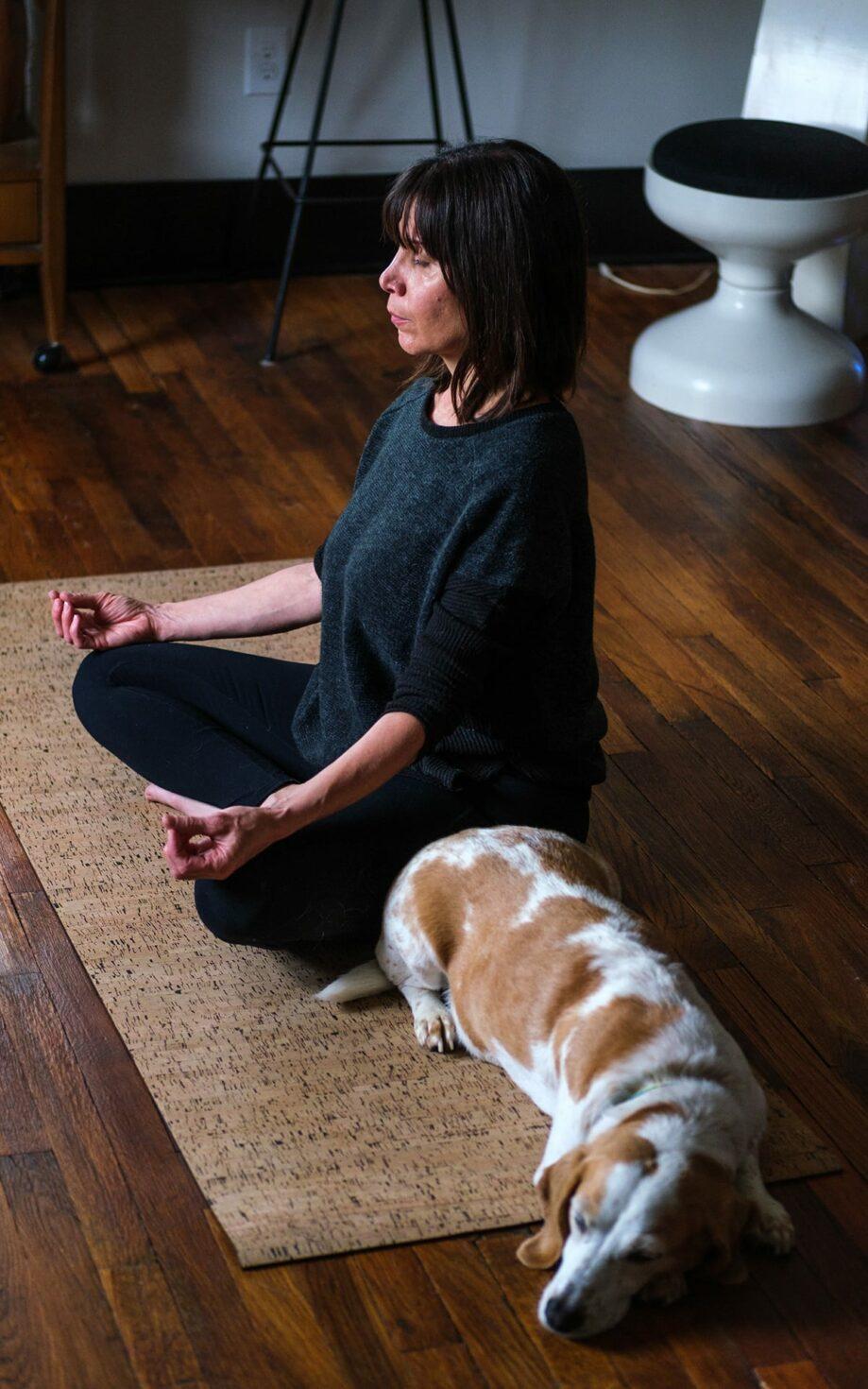 A woman meditating next to a sleeping dog