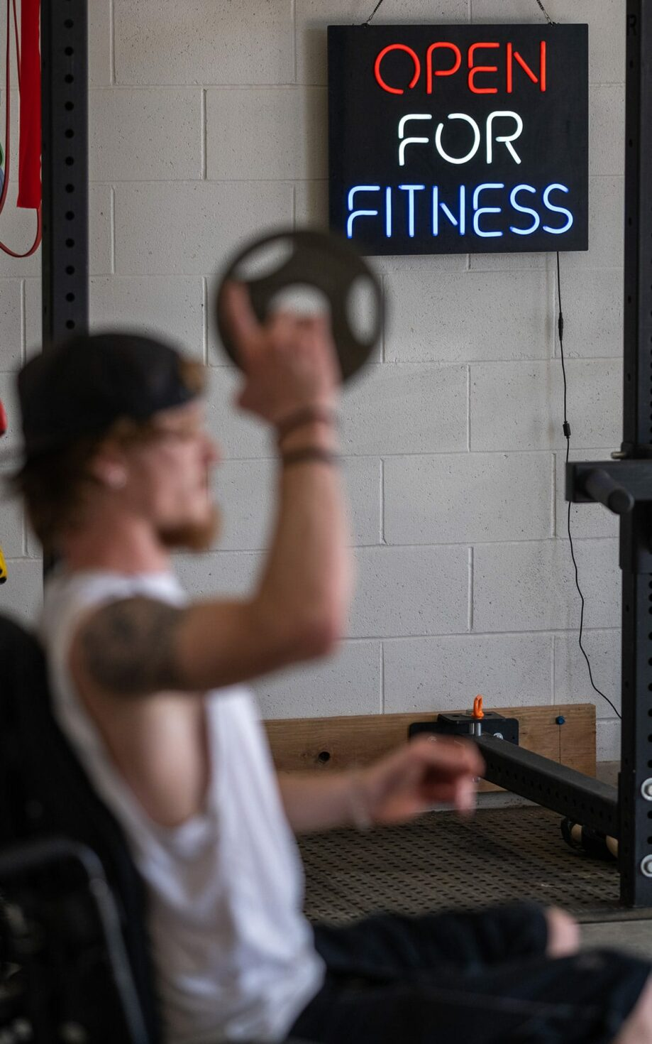A man exercises in front of a sign that reads 'open for business'