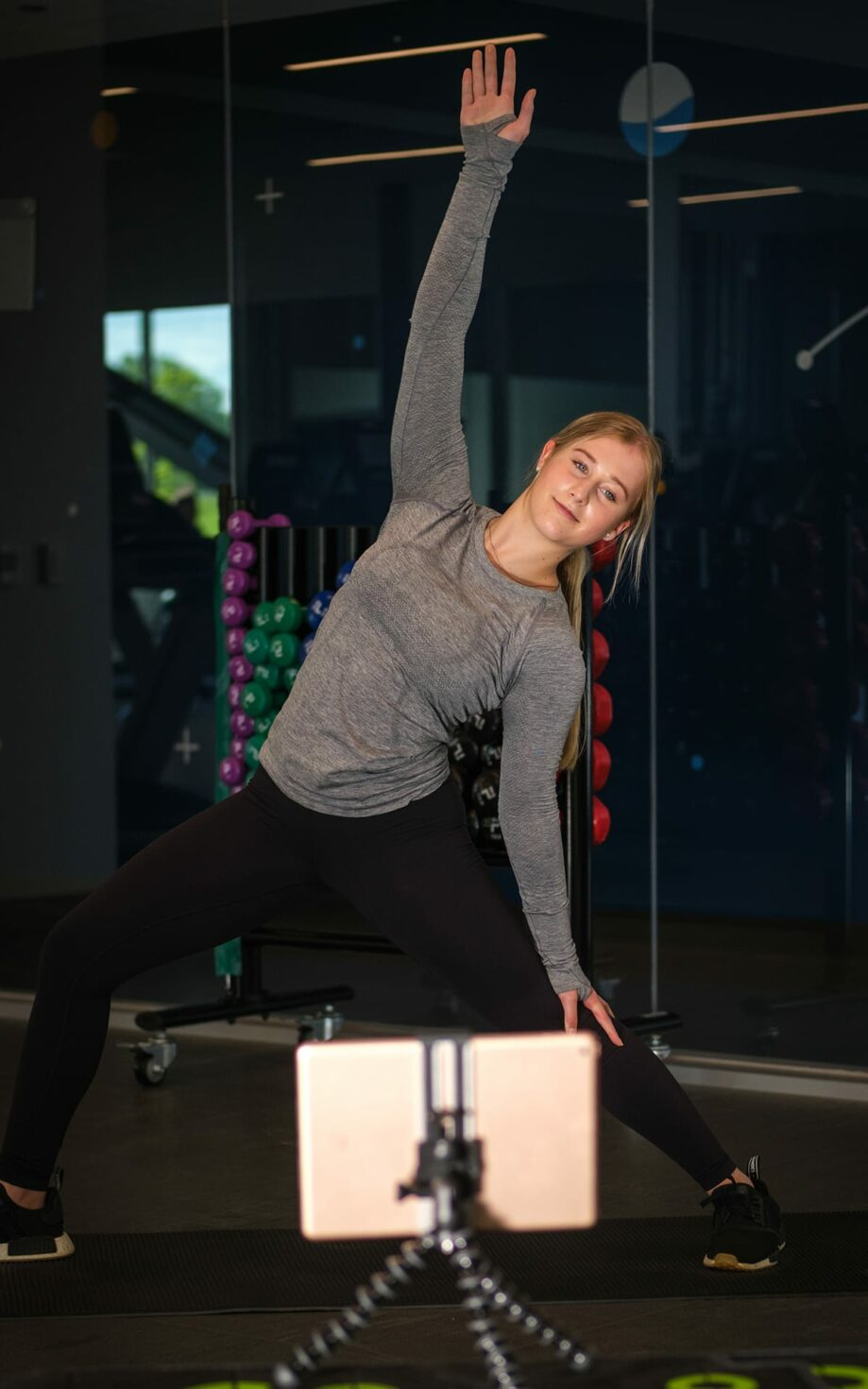An instructor demonstrating stretching via videoconference