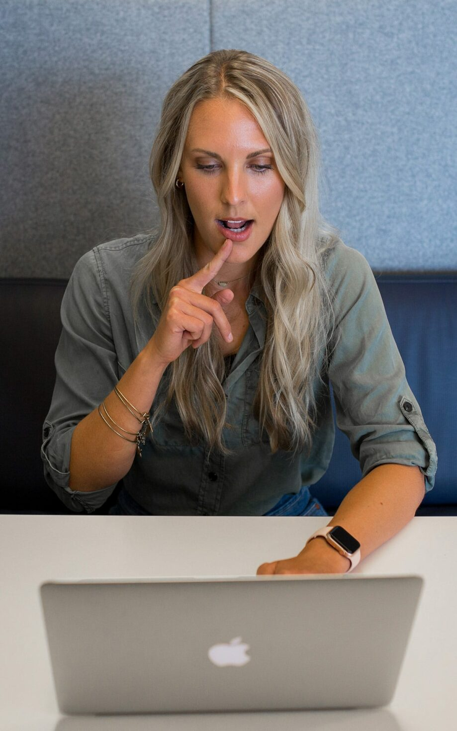 A therapist pointing to her mouth during a videoconference call