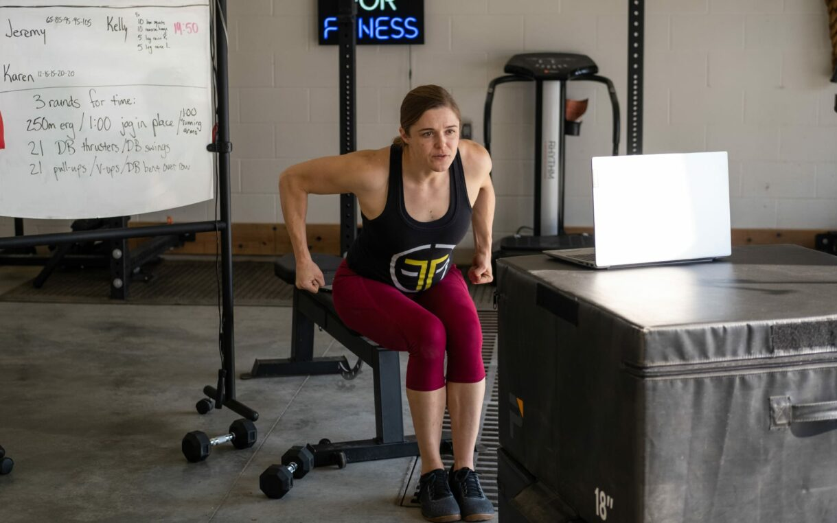 A trainer demonstrating weight lifting techniques via videoconference