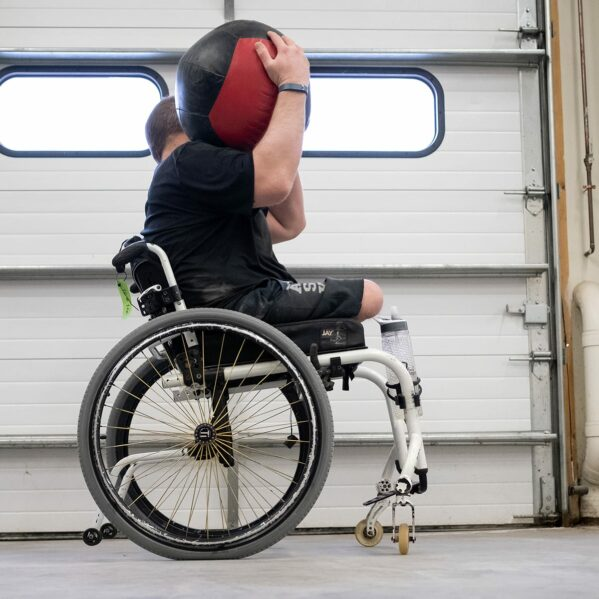 A man lifts a large medicine ball while in a wheelchair